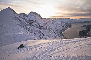 Norway, Lyngen, Skier skiing downhill at sunset - FFF001294