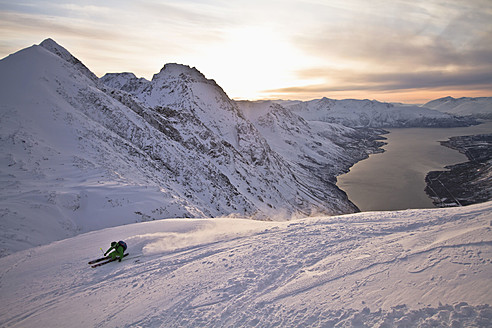 Norway, Lyngen, Skier skiing downhill at sunset - FFF001294