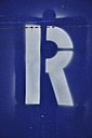 White spray paint letter R on blue, close up - AXF000028