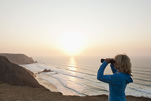 Portugal, Algarve, Sagres, Senior woman looking at beach through binocular - MIRF000444