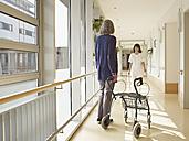 Germany, Cologne, Senior women holding walking frame in corridor, caretaker in background - WESTF018696