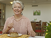 Germany, Cologne, Senior woman eating at table in nursing home - WESTF018702