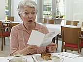 Germany, Cologne, Senior woman with card in nursing home - WESTF018708