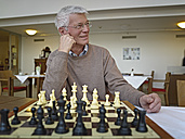 Germany, Cologne, Senior man playing chess in nursing home - WESTF018717