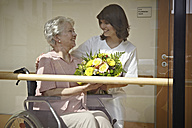 Germany, Cologne, Caretaker giving bouquet to senior women on wheelchair in nursing home - WESTF018720