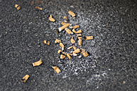 Germany, Frankfurt, Cigarette butt on road - MUF001198