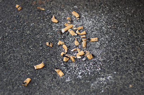 Germany, Frankfurt, Cigarette butt on road - MUF001198
