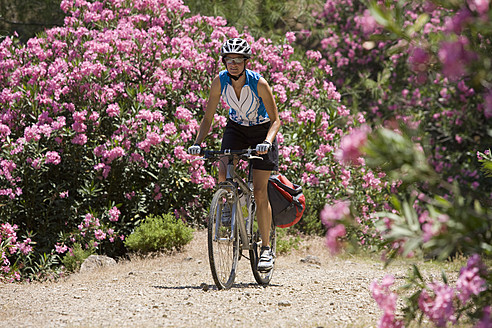 Turkey, Mid adult woman cycling through dirt track - DSF000564