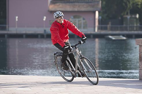Italy, Trento, Mature man cycling through promenade - DSF000571