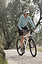 Italy, Trento, Mid adult woman cycling through dirt track - DSF000573