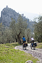 Italy, Trento, Man and woman cycling, Castle of Arco in background - DSF000574