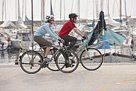 Italy, Trento, Man and woman cycling by harbour in Riva - DSF000615