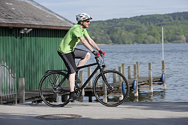 Germany, Bavaria, Starnberg, Mature man cycling by pier - DSF000600