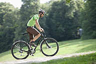 Germany, Bavaria, Munich, Young man cycling through single track - DSF000606