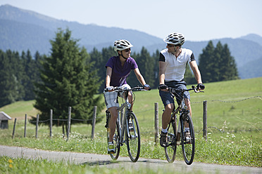 Germany, Bavaria, Man and woman cycling through country road - DSF000582