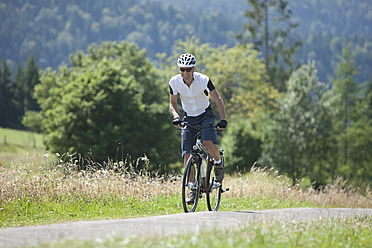 Germany, Bavaria, Young man cycling through country road - DSF000584