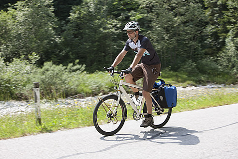 Austria, Tyrol, Young man cycling through country road - DSF000586