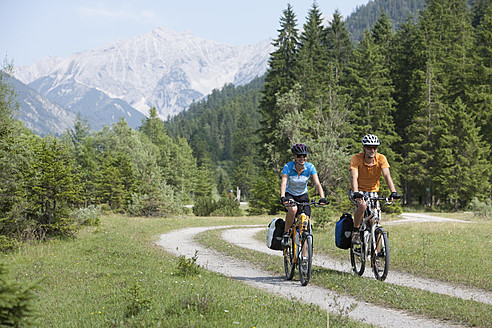 Austria, Tyrol, Man and woman cycling through dirt track - DSF000588