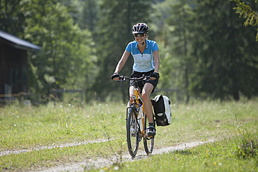 Austria, Tyrol, Young woman cycling through single track - DSF000591