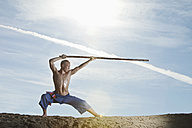 Germany, Bavaria, Young man doing martial arts training with stick - MAEF004662