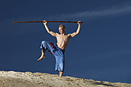 Germany, Bavaria, Young man doing martial arts training with stick - MAEF004677