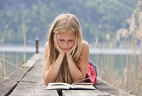 Austria, Teenage girl lying and reading book on jetty - WWF002387