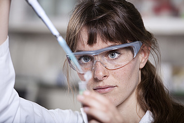 Germany, Bavaria, Munich, Scientist with pipette and test tube in laboratory - RBF000887