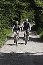 Germany, Bavaria, Senior couple cycling through single track - TCF002643