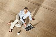 Germany, Berlin, Senior man using laptop - FMKYF000022