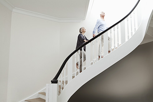 Germany, Berlin, Senior couple climbing stairway - FMKYF000052