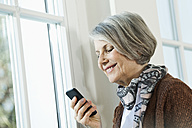 Germany, Berlin, Senior woman using cell phone, smiling - FMKYF000070