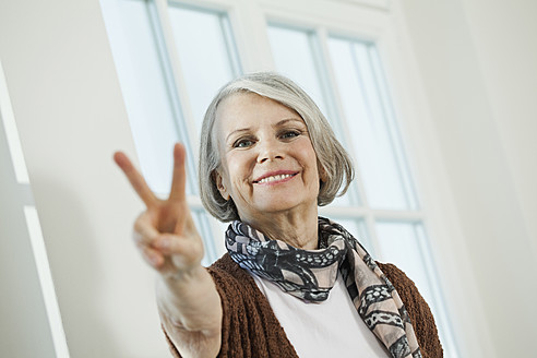 Germany, Berlin, Senior woman showing peace sign, smiling, portrait - FMKYF000073