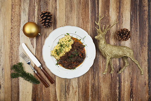 Plate of cooked venison goulash with mashed potatoes and Christmas decoration on wooden background - GWF001830