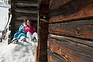 Austria, Salzburg, Young couple sitting in front of alpine hut - HHF004190