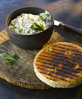 bowl of tzatziki with grilled bread on wooden board, close up - KSWF000827
