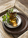 Black Tea with fresh peppermint on plate, close up - KSWF000828