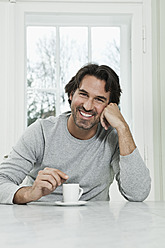 Germany, Berlin, Mature man with coffee cup, smiling, portrait - FMKYF000112