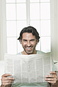 Germany, Berlin, Mature man with newspaper, smiling, portrait - FMKYF000115