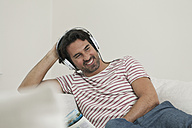Germany, Berlin, Mature man listening music with head phones - FMKYF000118