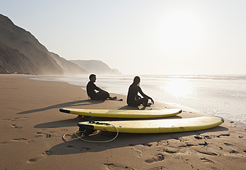 Portugal, Couple sitting on beach by surfboard - MIRF000460