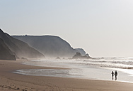 Portugal, Couple walking on beach - MIRF000463