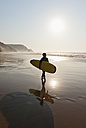 Portugal, Surfer walking on beach - MIRF000472