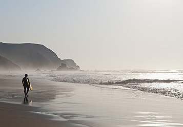 Portugal, Surfer walking on beach - MIRF000475