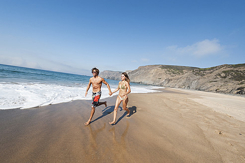 Portugal, Couple running on beach - MIRF000484