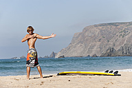 Portugal, Surfer standing by surfboard - MIRF000487