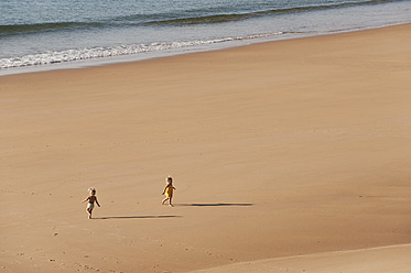 Portugal, Boy and girl running on beach - MIRF000499