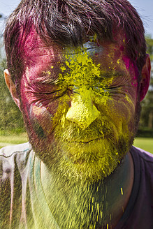 India, Ahmedabad, Man celebrates Holi festival with powder paints - MBEF000352