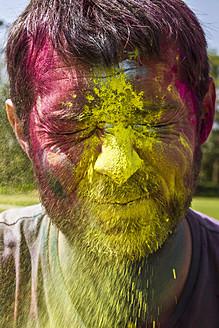 India, Ahmedabad, Man celebrates Holi festival with powder paints - MBEF000352