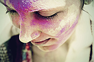 India, Ahmedabad, Young woman celebrating holi festival with powder paint - MBEF000366