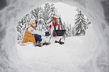 Austria, Salzburg, Young women sitting at fire place in winter - HHF004212